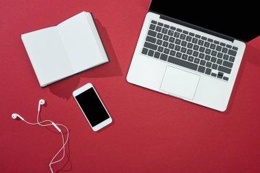 Top view of smartphone, laptop, earphones, blank notebook on red background stock vector