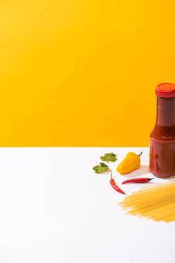 Bottle of tasty ketchup with peppers and raw spaghetti on white surface on yellow background stock vector