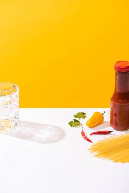 Bottle of ketchup beside peppers, raw spaghetti and glass of water on white surface on yellow background stock vector