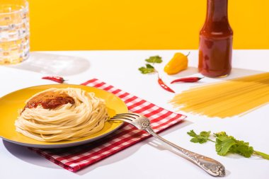 Selective focus of homemade spaghetti with ketchup, cilantro and peppers on white surface on yellow background stock vector