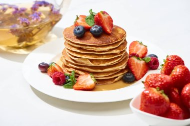 selective focus of delicious pancakes with honey, blueberries and strawberries on plate on white surface