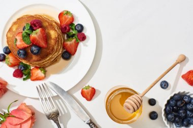 top view of delicious pancakes with honey, blueberries and strawberries on plate near cutlery and rose on marble white surface
