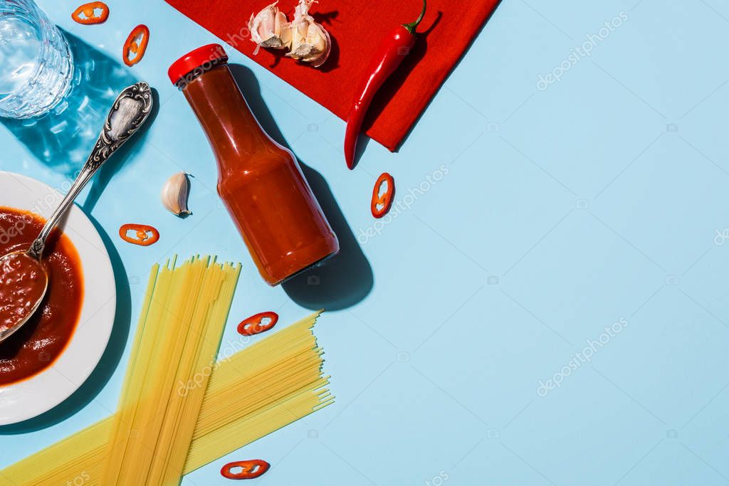 Top view of spicy ketchup with garlic and chili pepper beside spaghetti on blue background stock vector