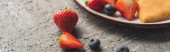 Photo close up view of fresh berries near delicious heart shaped pancakes on grey concrete surface, panoramic shot