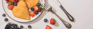 top view of delicious heart shaped pancakes with berries near cutlery on white background, panoramic shot