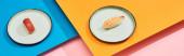 friss nigiri tonhallal és garnélarákkal kék, rózsaszín, narancssárga felületen, panorámás felvétel