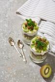 čerstvá granola s kiwi a jogurtem na šedém betonovém povrchu s pruhovaným ubrouskem a lžícemi