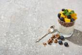 friss granola őszibarackkonzervvel, áfonyával és chia maggal szürke betonfelületen kanállal