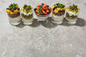 Fotografie delicious granola in glasses with fruits and berries on grey concrete surface
