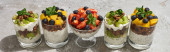 delicious granola in glasses with fruits and berries on grey concrete surface, panoramic shot