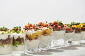 selektivní zaměření lahodné granoly ve sklenicích s ovocem a bobulemi na šedém betonovém povrchu izolovaném na bílém