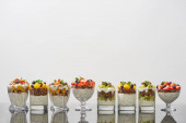 Photo delicious granola in glasses with fruits and berries isolated on white