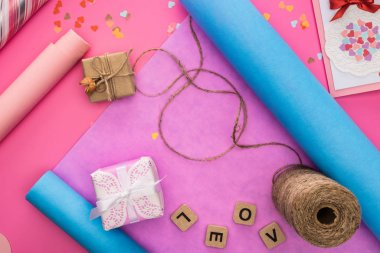 top view of valentines decoration, wrapping paper, twine, gift boxes, greeting card and love lettering on wooden cubes on pink background
