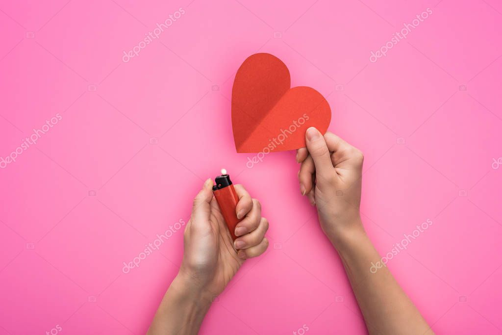 Cropped view of woman lighting up empty red paper heart with lighter isolated on pink stock vector
