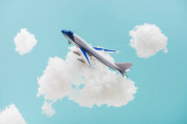 Photo toy plane flying among white fluffy clouds made of cotton wool isolated on blue