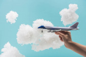Photo cropped view of woman playing with toy plane among white fluffy clouds made of cotton wool isolated on blue