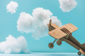 Fotografie wooden toy plane flying among white fluffy clouds made of cotton wool isolated on blue