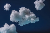 white fluffy clouds made of cotton wool isolated on dark blue