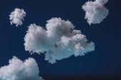 weiße flauschige Wolken aus Watte isoliert auf dunkelblau