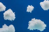 dřevěná hračka letadlo létání mezi bílými nadýchané mraky z bavlněné vlny izolované na modré