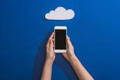 oříznutý pohled na ženu držící smartphone v blízkosti prázdné bílé papírové mraky na modré
