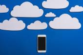felső nézet fehér papír vágott felhők és okostelefon kék háttér