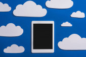 top view of white paper cut clouds and digital tablet on blue background