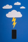 horní pohled na bílý papír řezané mraky s osvětlením bít smartphone na modrém pozadí