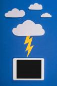 horní pohled na bílý papír řezané mraky s osvětlením bít digitální tablet na modrém pozadí