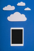 felső nézet fehér papír vágott felhők és digitális tabletta kék alapon