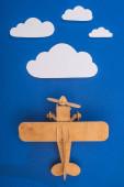 vrchní pohled na dřevěné hračky letadlo na modré obloze s papírem řezané bílé mraky