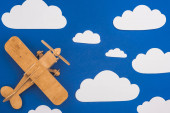 Photo top view of wooden toy plane in blue sky with paper cut white clouds