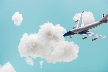 Toy plane flying among white fluffy clouds made of cotton wool isolated on blue stock vector