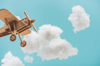 Wooden toy plane flying among white fluffy clouds made of cotton wool isolated on blue stock vector