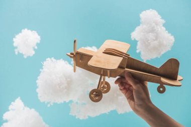 wooden toy plane flying among white fluffy clouds made of cotton wool isolated on blue