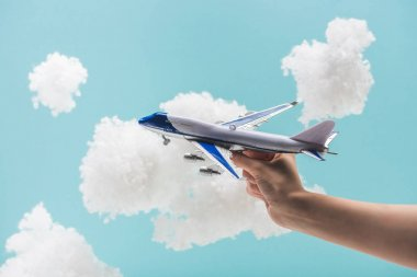 Cropped view of woman playing with toy plane among white fluffy clouds made of cotton wool isolated on blue stock vector