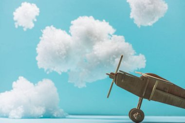 Wooden toy plane among white fluffy clouds made of cotton wool isolated on blue stock vector