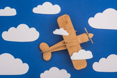 Top view of wooden plane in blue sky with paper cut white clouds stock vector