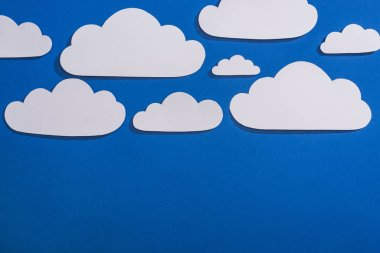 Top view of white paper cut clouds on blue background stock vector
