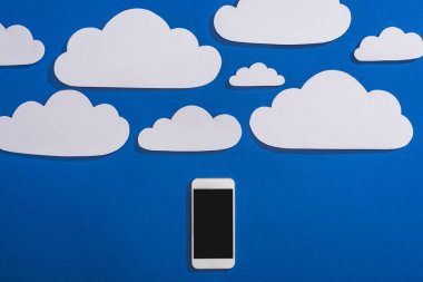 Top view of white paper cut clouds and smartphone on blue background stock vector