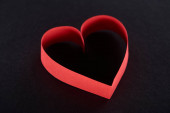 Fotografie Red paper in heart shape isolated on black