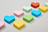 Colorful decorative papers in heart shape on grey background