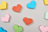 Top view of festive heart shaped papers on grey background