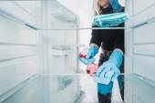 Oříznutý pohled na ženu v gumových rukavicích čištění chladničky s detergentem izolované na bílém
