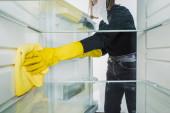 Oříznutý pohled na ženu v gumových rukavicích čištění chladničky s hadrem izolované na bílém