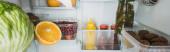 Panoráma felvétel friss gyümölcsökről, káposzta szeletekkel és szószokkal a hűtőszekrényben