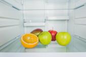 Čerstvá jablka s mangem a plátkem pomeranče na chladničce
