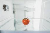 Čerstvé rajče na poličce chladničky s otevřenými dveřmi izolované na bílém