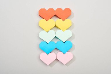 Top view of colorful heart shaped papers on grey background stock vector