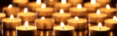 selective focus of burning candles glowing in darkness, panoramic shot